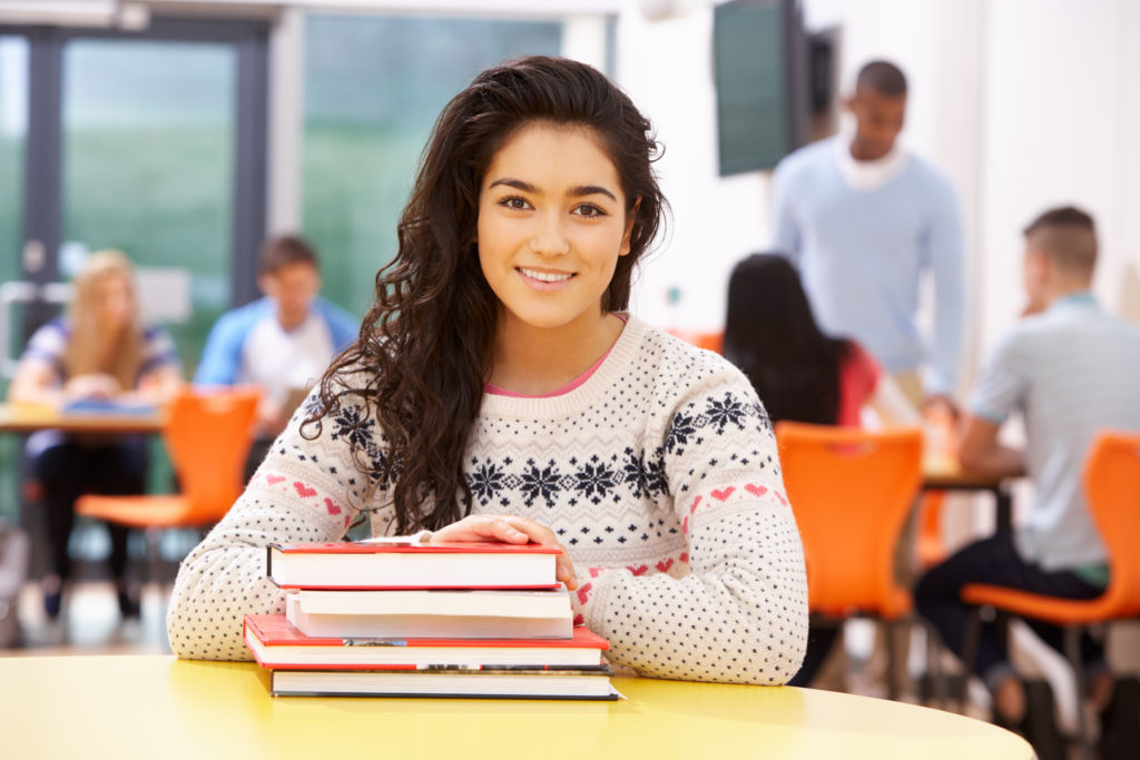 Female Teenage Student In Classroom With Books